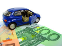 Car expenses. Blue car over euro notes. Shallow DOF Royalty Free Stock Photos
