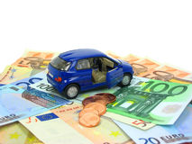 Car expenses. Blue car over euro notes and coins isolated Stock Photography