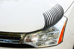 Car Eyelashes on Left Headlight. Car eyelashes car accessory with eye liner on white car. View of left headlight from front Stock Photos