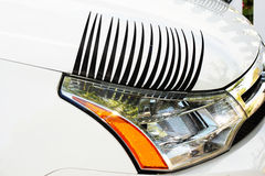 Car Eyelashes on Right Headlight. Car eyelashes car accessory with eye liner on white car. View of right headlight from side Stock Images
