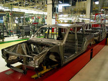 Car factory. New car on the line in factory stock photography
