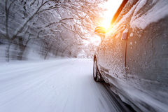 Car and falling snow in winter on forest road with much snow. (Motion blur stock photography