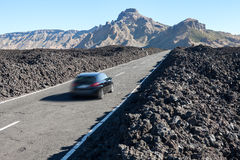 Car fast driving on the route TF-38 in the middle of volcanic lava pebbles on asphalt road. Canary, Tenerife Royalty Free Stock Image