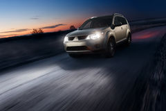 Car fast speed drive on asphalt road at dusk Royalty Free Stock Photography