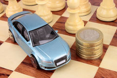 Car Finance Business. A blue luxury car on a chess board next to a stack of Euro coins. A metaphor for a car finance decision Stock Image
