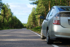 Car on Finnish road in the forest. Asphalt road is running through the Finnish forest. Modern car is parked aside from the route. Highway is photographed with Stock Photo