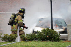 Car fire. A photo of a firefighter spraying water on a car that is on fire Stock Photo