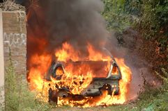 Car on fire in alley way Stock Photography