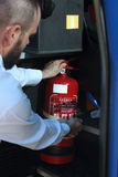 Car fire extinguisher. The bus driver checks the fire extinguisher stock photos