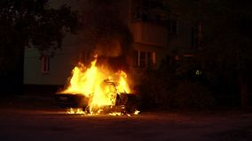 Car on fire near a residential building explodes and continues to burn. Theme of riots criminal arson of a car near house. Trees close to burning sedan. A man stock video footage