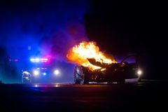 Car on fire at night with police lights in background stock photos