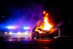 Car on fire at night with police lights in background. At night stock images