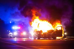 Car on fire at night with police lights in background. Noone stock photos