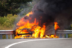 Car on fire with passengers. On highway Stock Photos