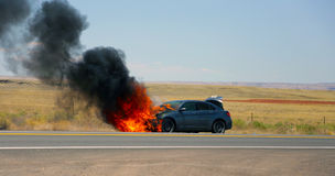 Car fire on the side of the road. Car Fire desert road Arizona sedan fire black smoke fully engulfed accident car totaled Royalty Free Stock Images