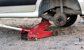 Car fixed in the garage, Hydraulic floor jack lift a car, Wheel without tire, Key cross road and four nuts Royalty Free Stock Photography