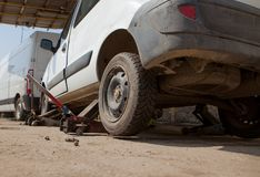 Car fixed in the garage, Hydraulic floor jack lift a car, Wheel without tire.  royalty free stock image