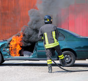 Car with flames and black smoke firefighter intervening to tampe Royalty Free Stock Photo
