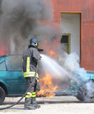 Car with flames and black smoke firefighter intervening to tampe Royalty Free Stock Photos