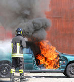 Car with flames and black smoke firefighter intervening to tampe Stock Images