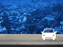 Car flat icon on wooden table over aerial of modern city tower, Royalty Free Stock Photos