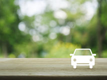 Car flat icon on wooden table over blur green tree background, B Royalty Free Stock Photo