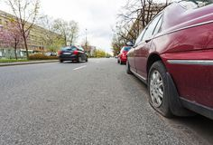 Car with flat tire. On the side of the street, passed by other car Stock Photos