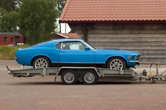 Car on a flatbed truck. Old cllasic car carrier trailer Royalty Free Stock Photos