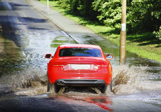 Car in flood water. Red car driving in flood water road royalty free stock photo