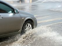 Car in floods. Flooding in the city with car and driving through the water Stock Photography