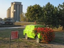 Car with flowers and silos. Bush of red flowers growing from green car`s engine; on the board is written: `Flowers in car is nicer than car on flowers - Maja stock image