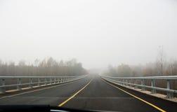 Car in a fog road Stock Photo