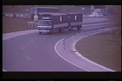 Car following truck off main highway stock video