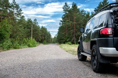 Car in the forest road. Black Offroad car in the forest road Stock Images