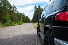 Car in the forest road. Black Offroad car in the forest road Stock Photo