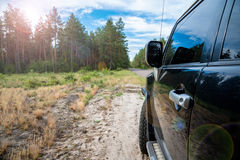 Car in the forest road. Black Offroad car in the forest road Stock Image