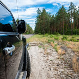 Car in the forest road. Black Offroad car in the forest road Royalty Free Stock Photos
