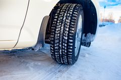 Car front corner, winter tire and the snowy city landscape in Russia stock photos