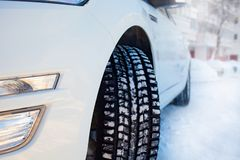 Car front corner, winter tire and the snowy city landscape in Russia stock photography