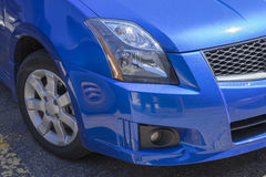 Car front end. Closeup of the nissan sentra blue car front end royalty free stock photo