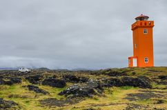 The car in front of orange lighthouse on the rocks in Iceland,. Snaefellsnes Peninsulain royalty free stock photos