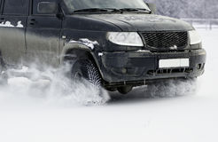 Car front wheels and headlights covered with icy snow Stock Photo