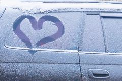 Car with frozen windows and a heart drawn on the glass. stock photo