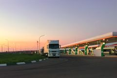 Car fueling station at dawn or in evening during sunset, truck in parking lot. stock photography