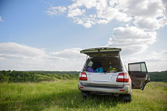 Car with full trunk of things standing in field Royalty Free Stock Photo