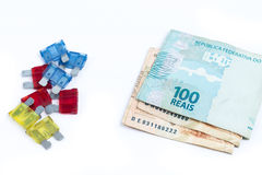 Car fuse. brazilian currency and pile of colorful electrical automotive fuses or circuit breakers Stock Image