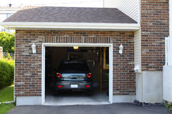 Car in the garage. SUV car in a garage next to the entrance to a house Royalty Free Stock Image