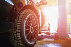 Car in garage of auto repair service with special repairing. Car in garage of auto repair service shop with special repairing equipment Stock Photography