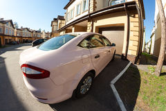 Car garage cottage. Pink car parked near garage of new cottage in a suburb residential area near Vladimir (Russia). Shot with a wide angle fish-eye lens Royalty Free Stock Image