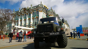 Car GAZ against the building of the Hermitage Museum in St. Petersburg during the celebration of the Victory parade Stock Photos